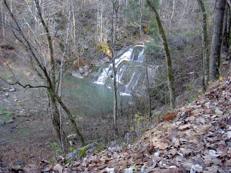 Joe Mill Creek Falls. Roadside at a very narrow gravel road. Concrete spillway where the creek flows over the road downstream.
